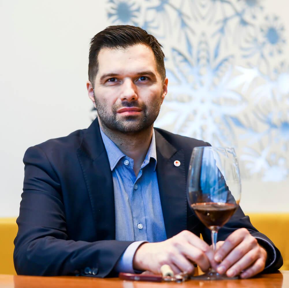 Szymon milonas trzymający wino